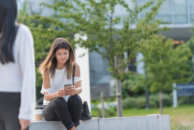 student using cellphone outside