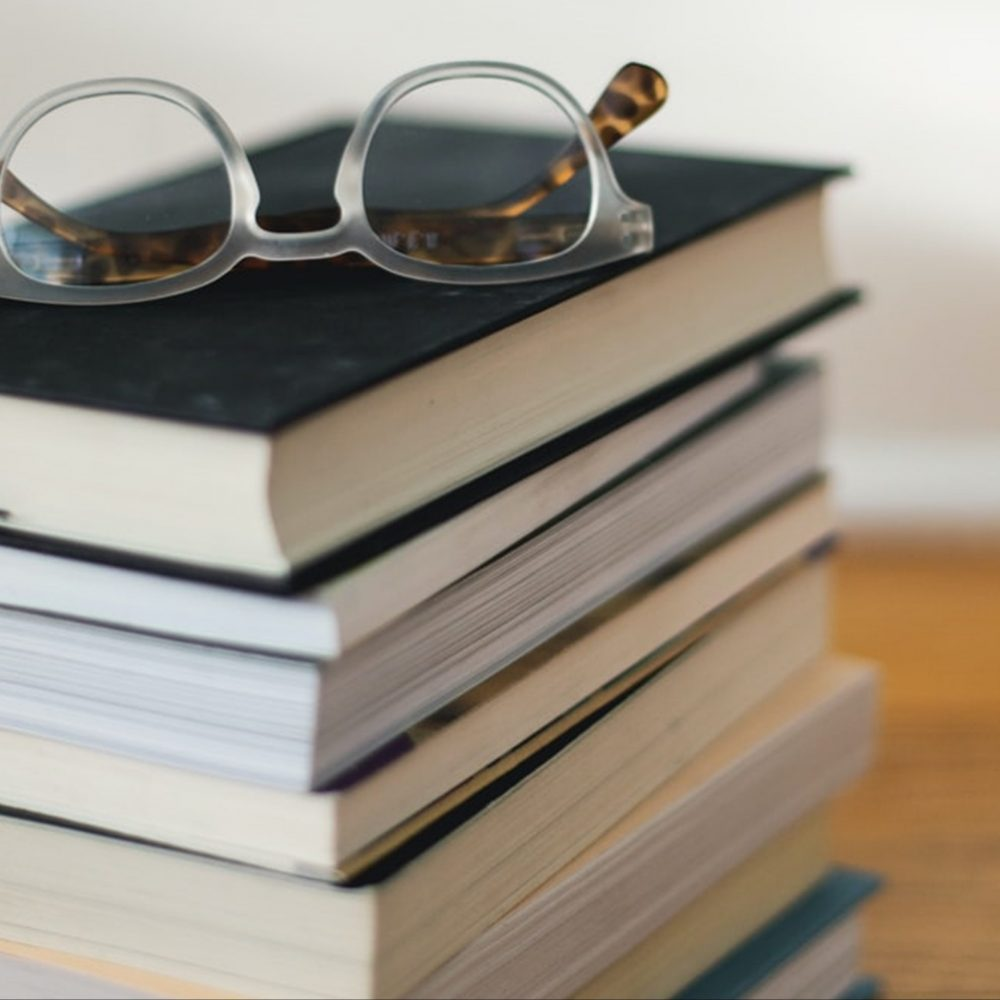 A stack of books sitting on a table. A pair of glasses rest on the top of the pile.