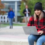 student outside with laptop