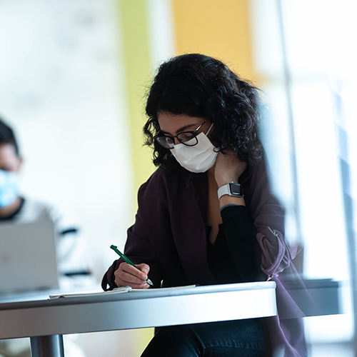 Student wearing mask and taking notes in front of an open laptop.