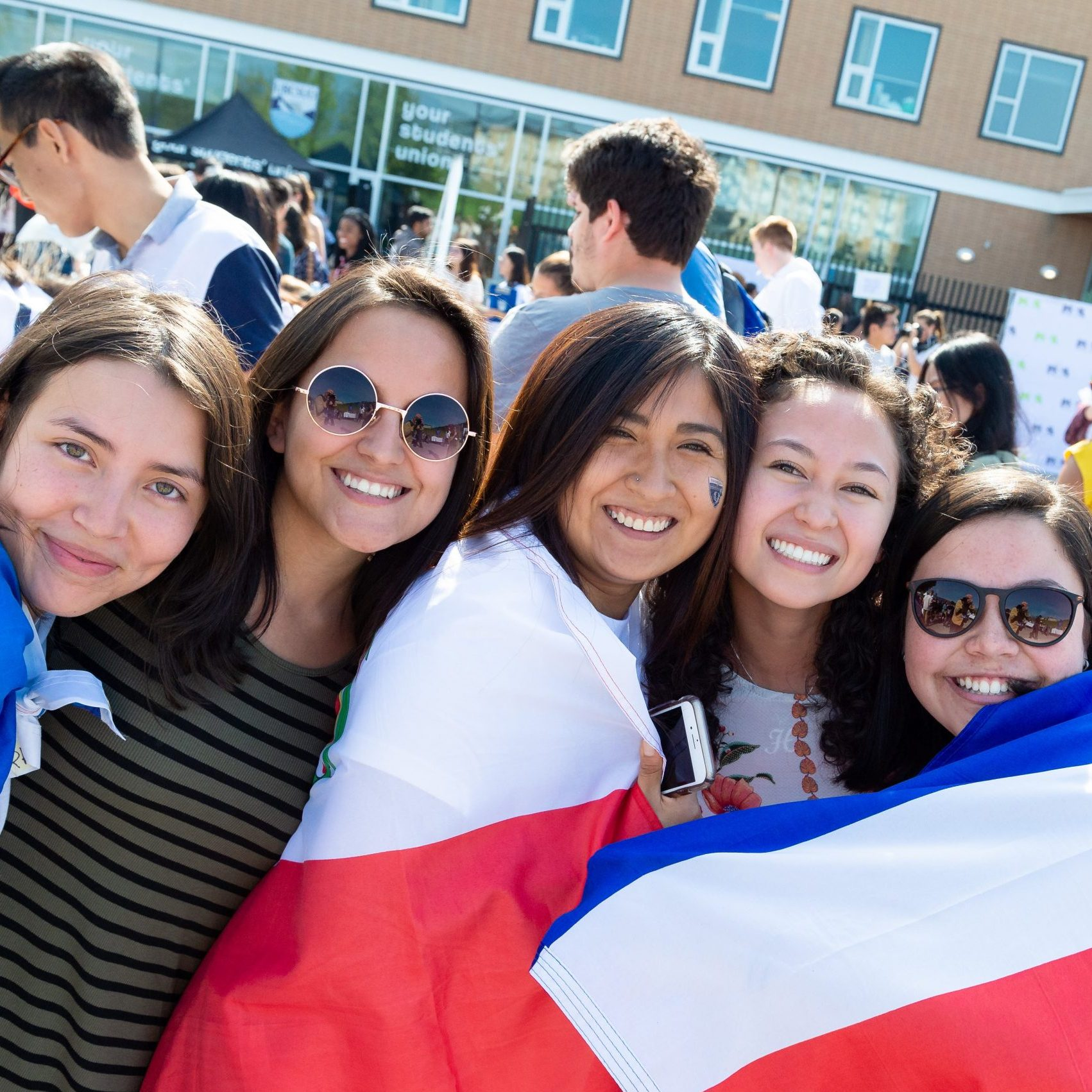 a group of students huddled for a photo and smiling with a flag wrapped around them